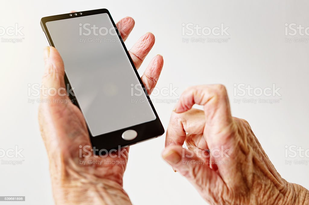 An old person\'s wrinkled hands hold a smartphone, one hand hovering...