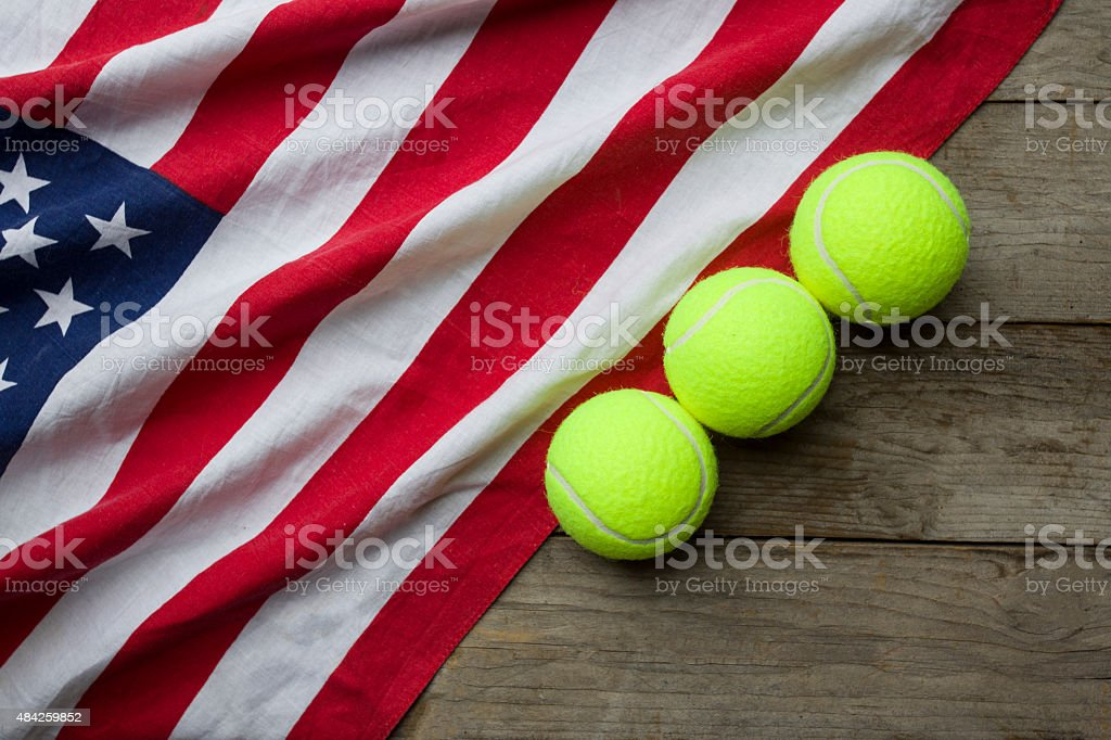 new tennis balls with an American flag on wood table stock photo