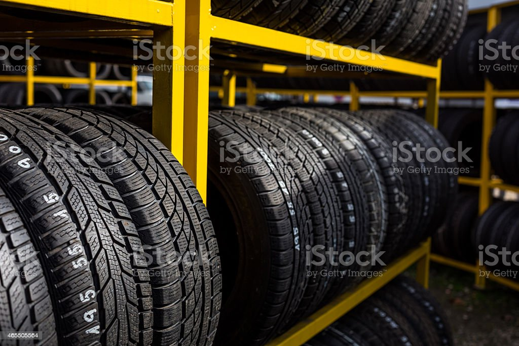 New tires on tire racks in a tire store stock photo