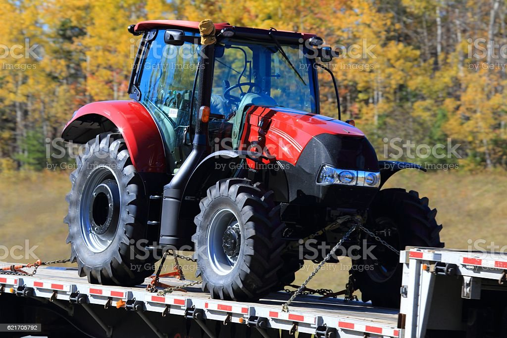 New tractor on a flatbed trailer, trees in the background. stock photo