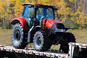 New tractor on a flatbed trailer, trees in the background.