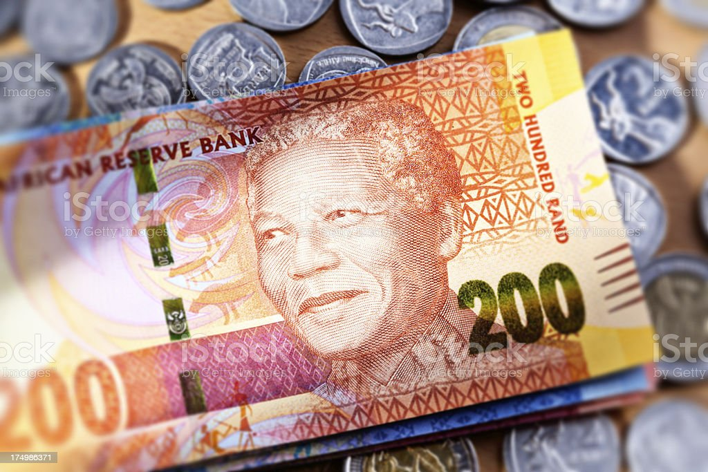 New Two Hundred Rand South African banknote resting on coins stock photo