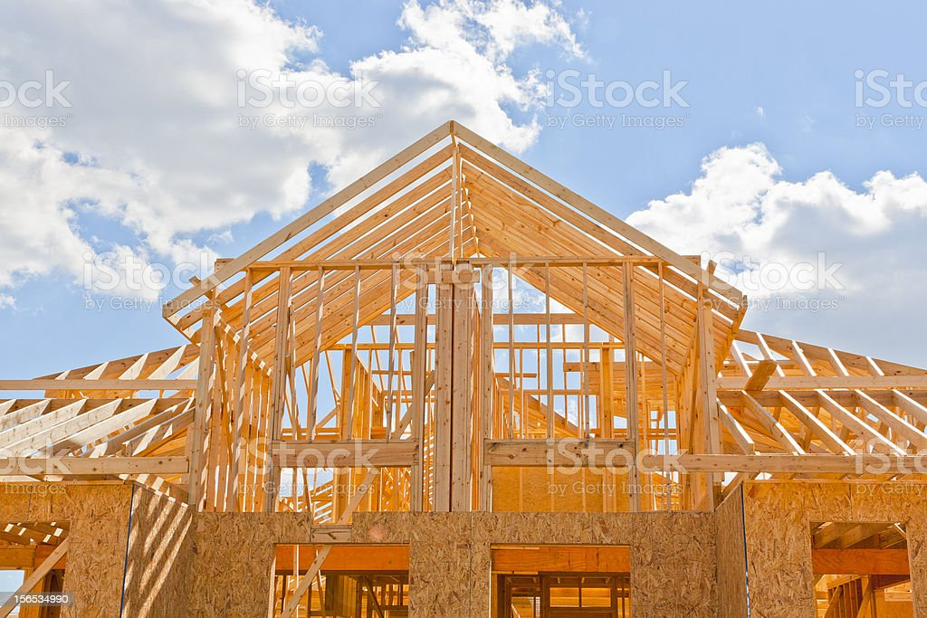 New two-story home construction framed blue sky background stock photo