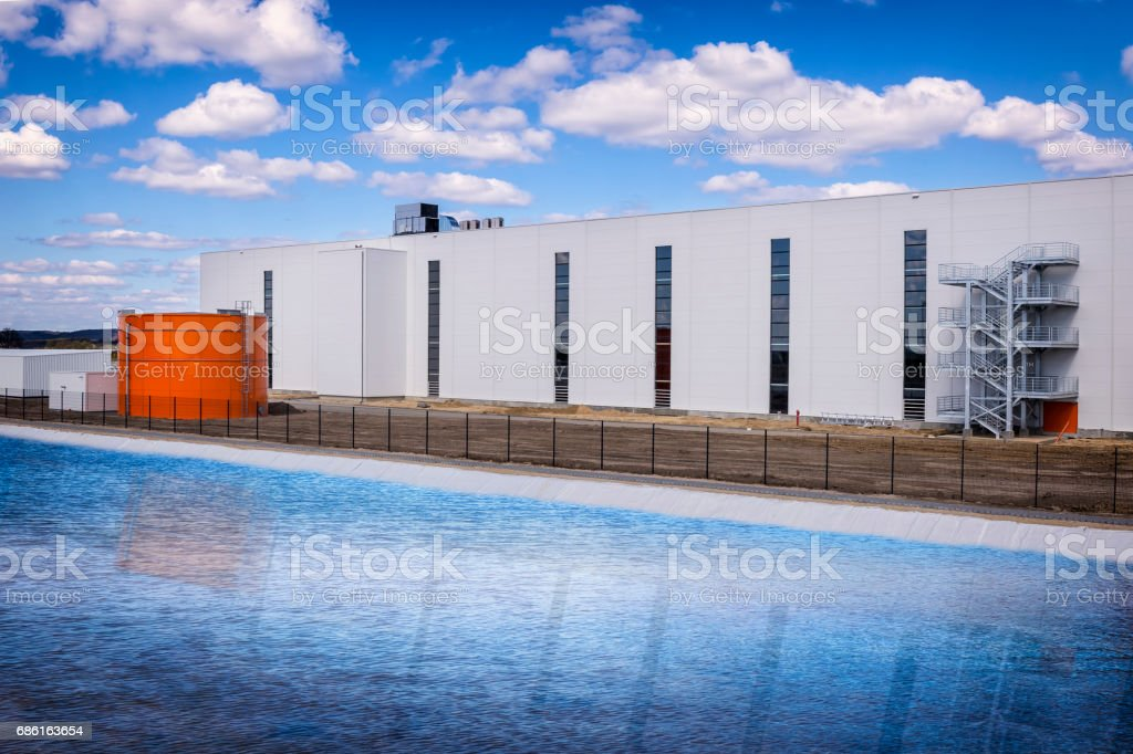 New warehouse building with large fire-fighting pool stock photo