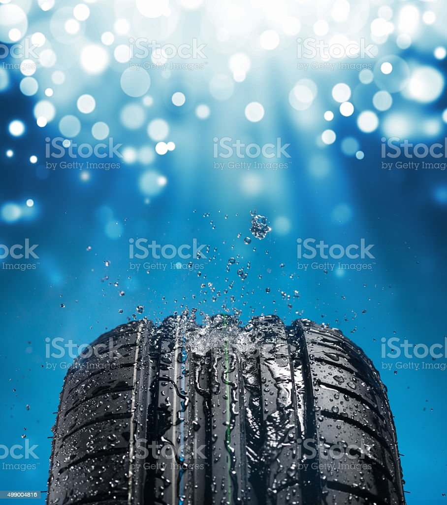 New wet tire while raining with blue light and sparkles stock photo
