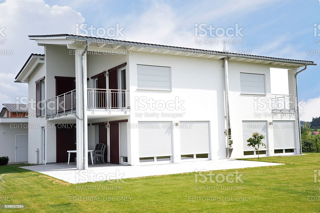 new white house - anonymous home with tidy garden reconstruction stock photo