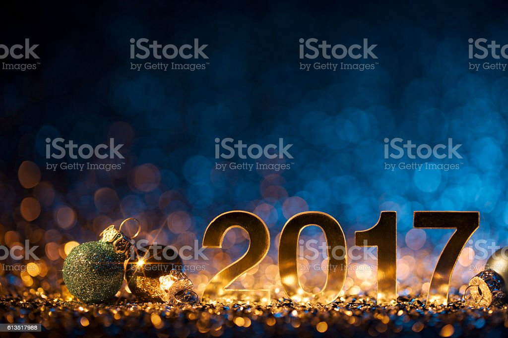 Golden numbers 2017 and christmas decorations on glitter and...
