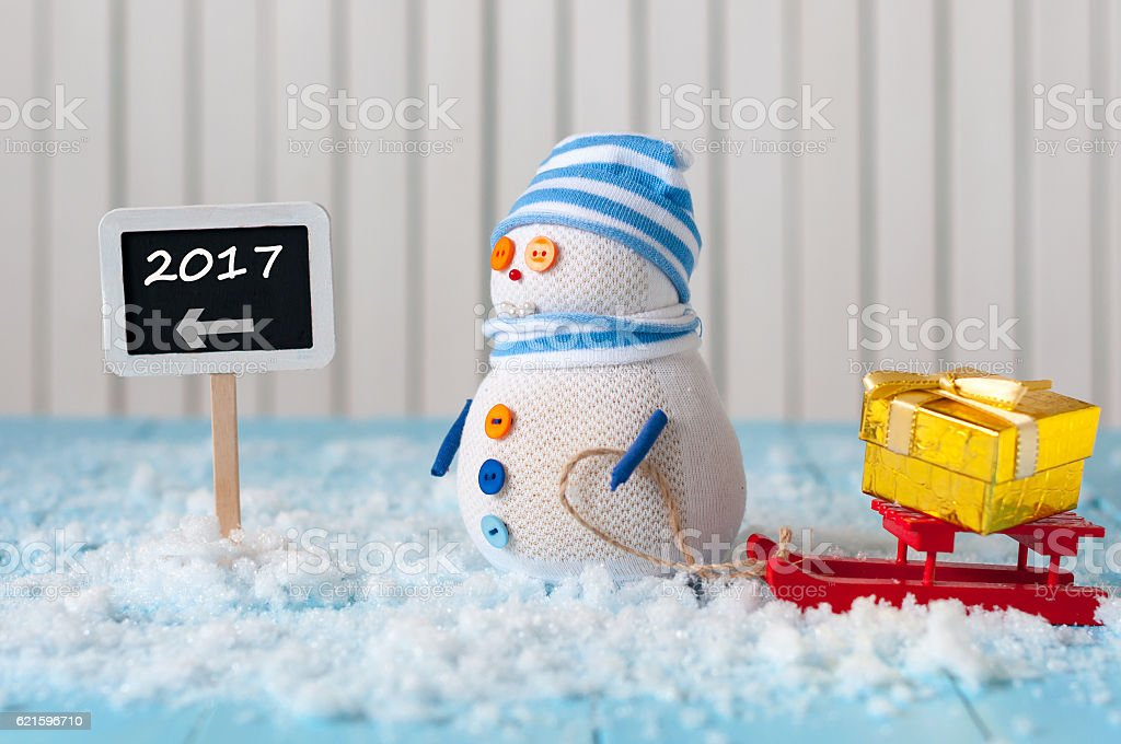 New Year 2017 is coming concept. Snowman with red sled stock photo