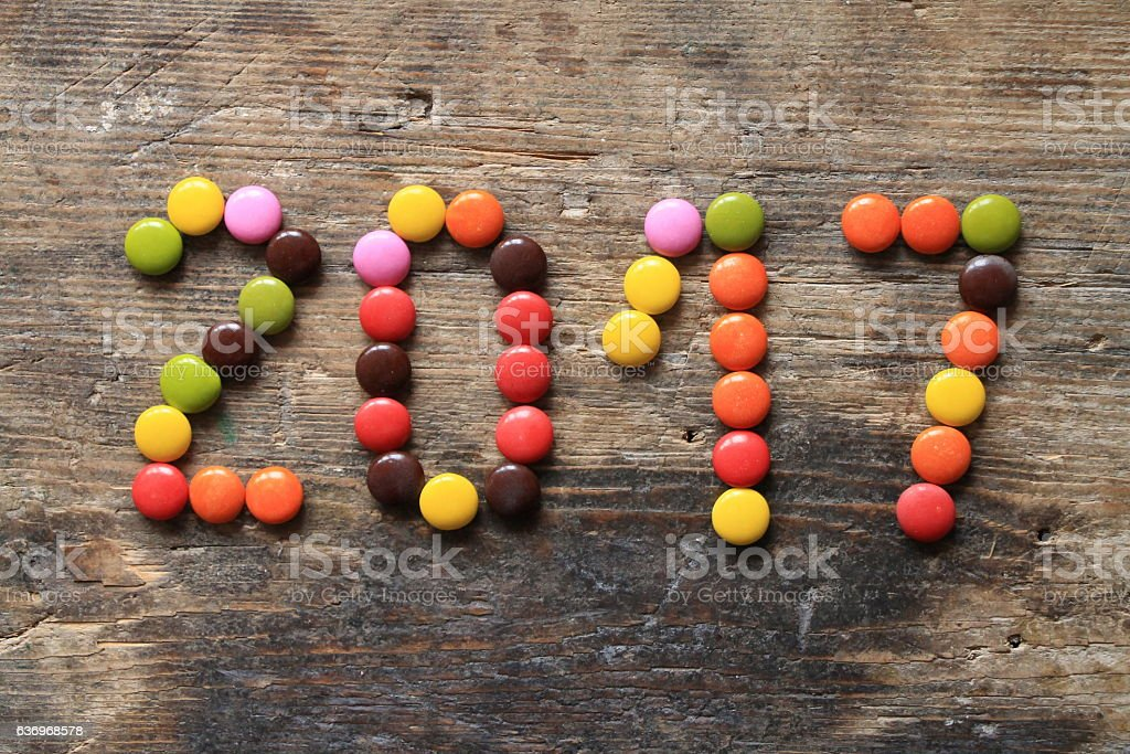 New Year 2017 made with colorful candies on wooden table stock photo