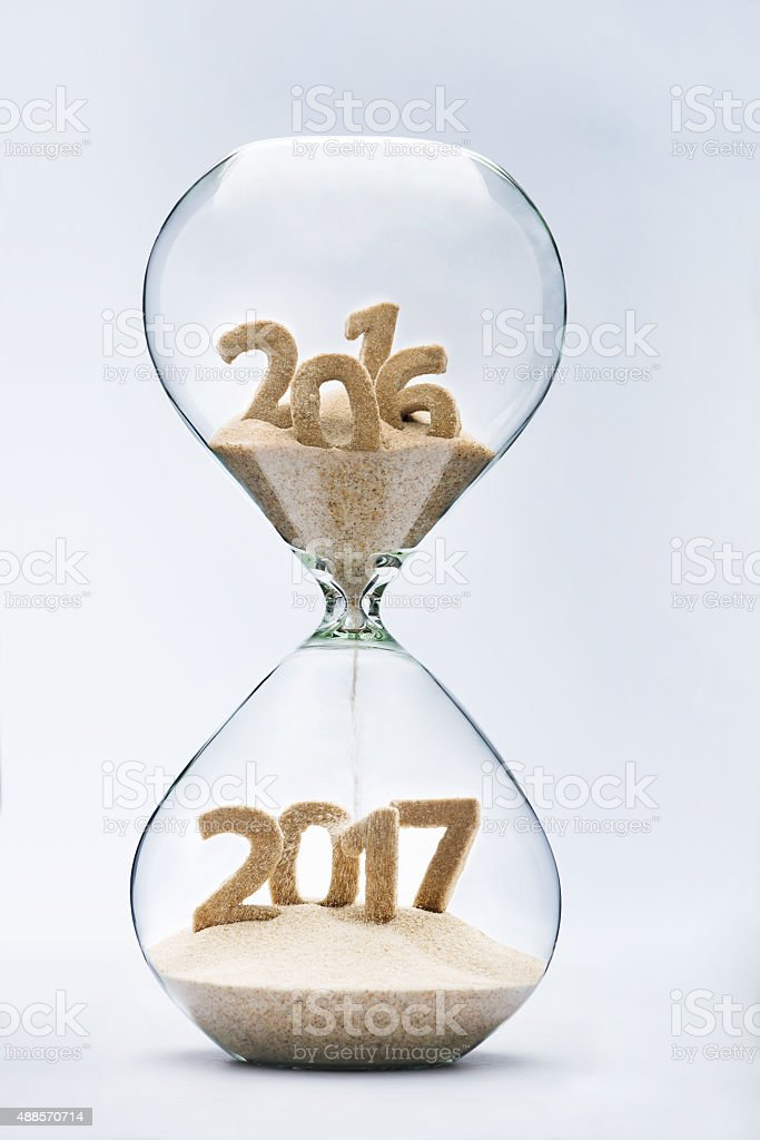 New Year 2016 concept with hourglass falling sand taking the shape of...