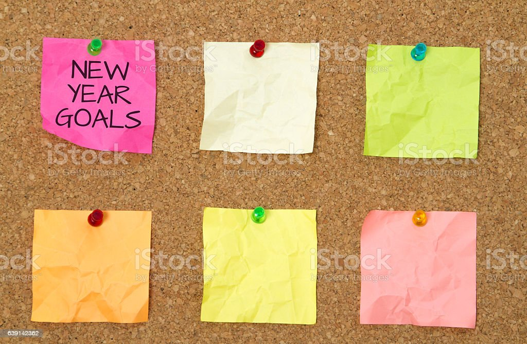 new year goals pinned on sticky notes against cork board stock photo