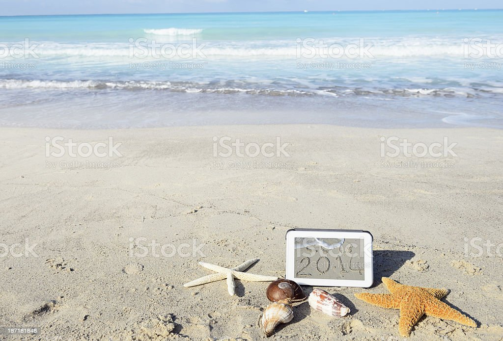 New Year Message on Tablet at the Beach. royalty-free stock photo