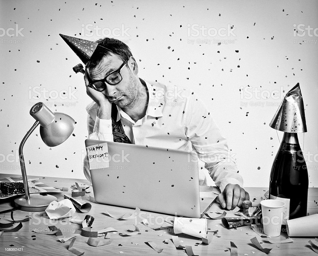 New Year Party, Birthday, hungover man behind laptop, office, retro royalty-free stock photo