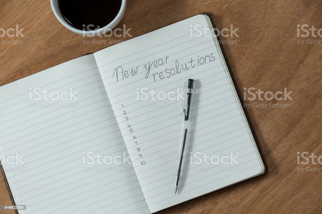New year resolutions written on diary with coffee mug stock photo