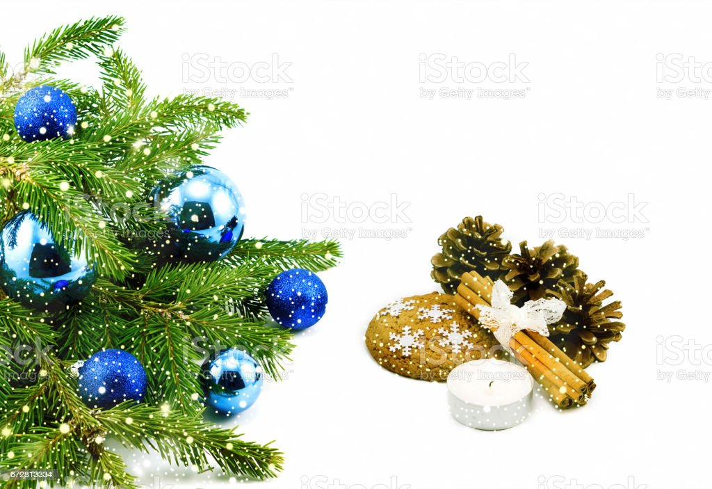New year theme: Christmas tree, blue balls, decorations, candle, snowflakes, cookies, cones, cinnamon isolated on white with shiny snowfall stock photo