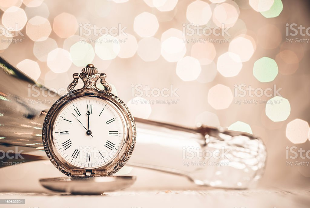 New Year\'s clock and champagne at midnight on abstract background