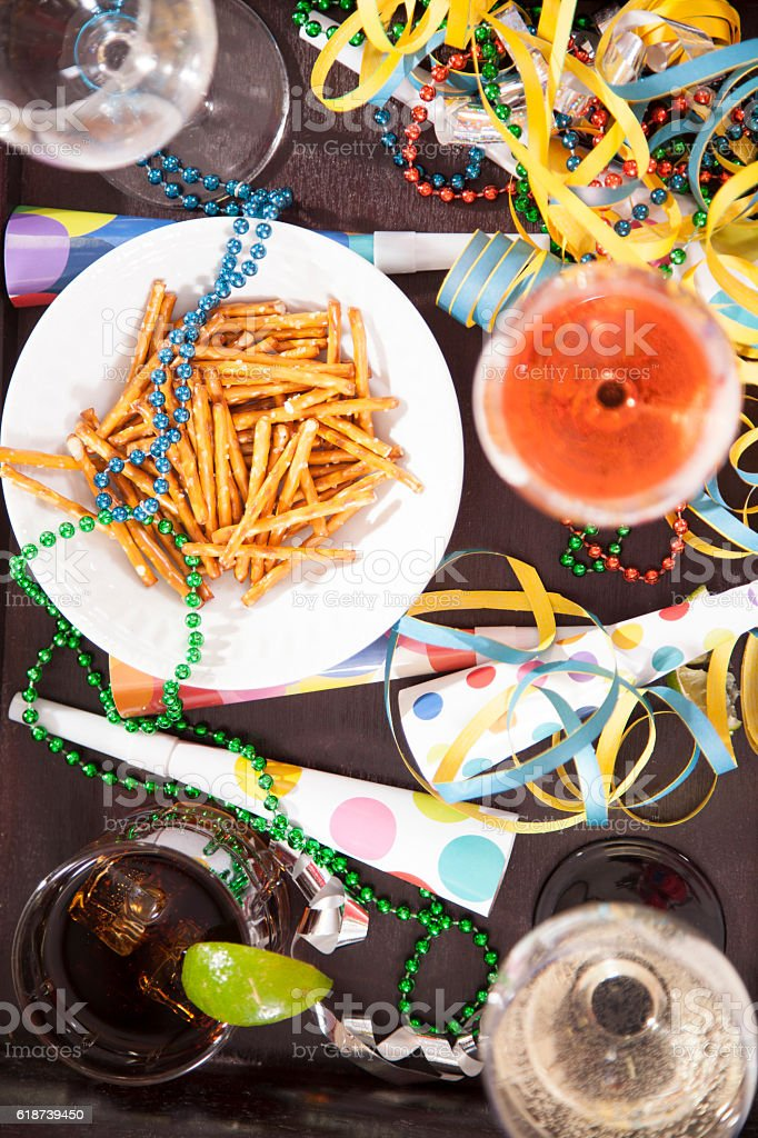 New Year's Eve party with drinks, snacks, confetti, blow horns. stock photo