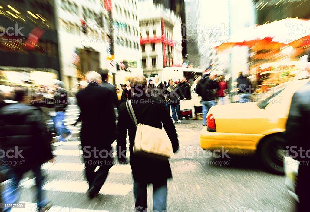 busy street. unrecognized pedestrians walking across the 5 th avenu...