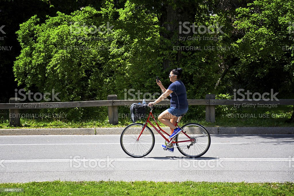 New York City Bicyclist Checking Cellphone Messages, Central Park, Manhattan royalty-free stock photo