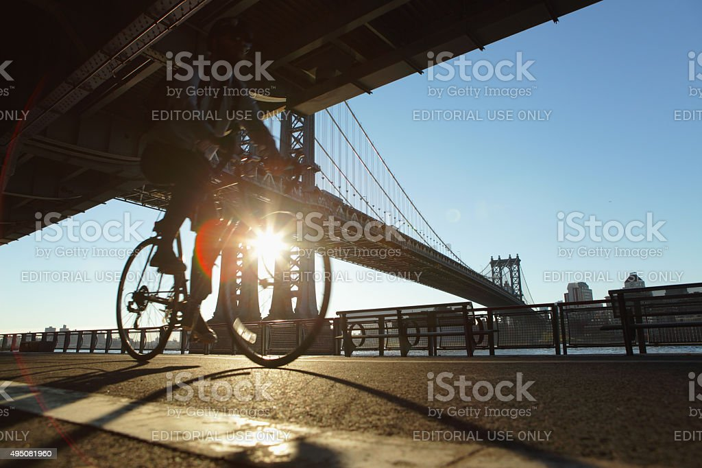 New York City cyclist rides down the East River Esplanade stock photo