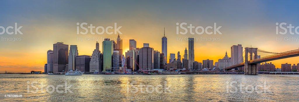 New York City downtown skyline and Brooklyn bridge at sunset stock photo