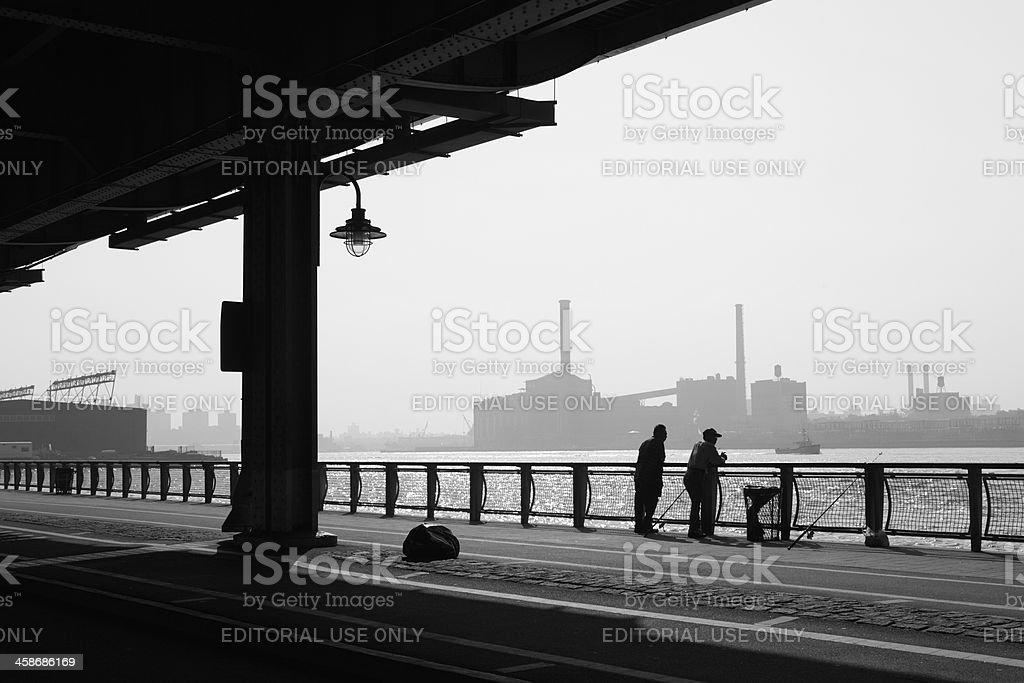 New York City fishing man and Manhattan Bridge stock photo