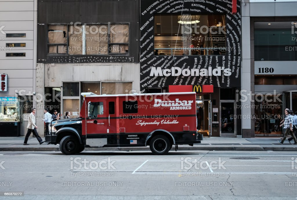 New York City, New York, USA - October 8 2016: Armoured delivery truck seen parked outside a famous fast food chain with the aim of collecting the takings from the restaurant. stock photo