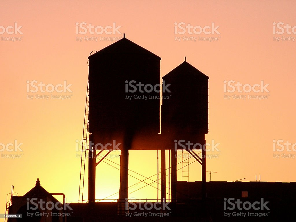 New York City rooftop water tanks at sunset, copy space royalty-free stock photo
