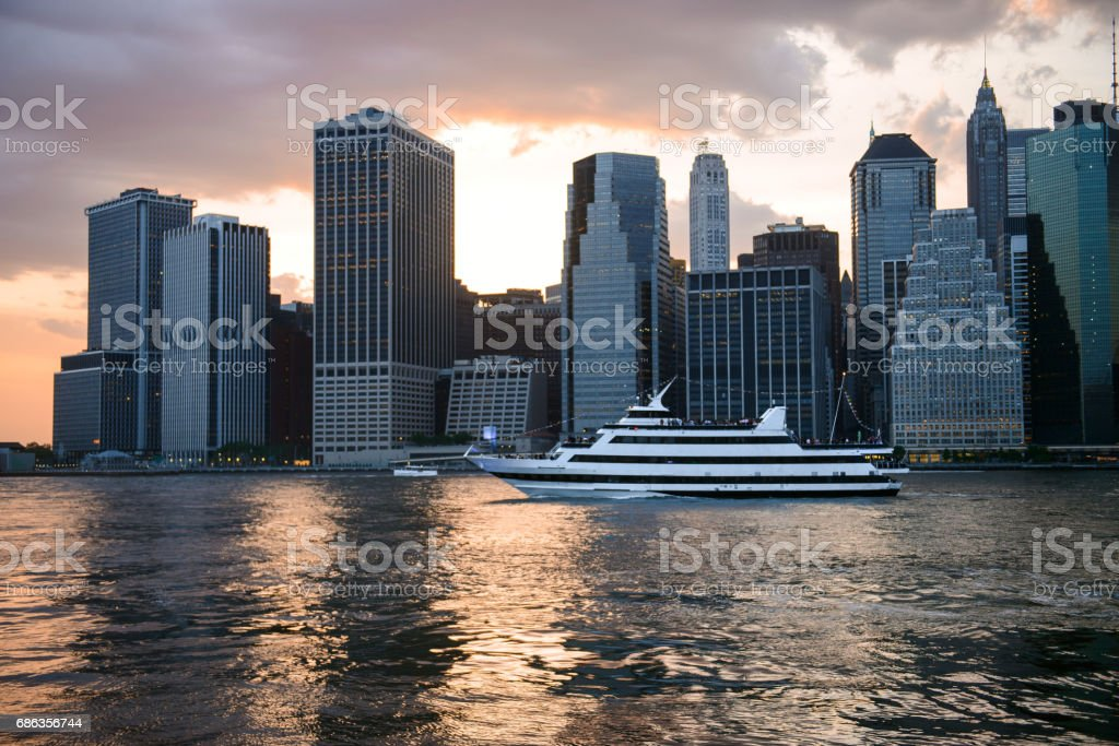 New York City skyline at sunset time and cruise ship with tourists.