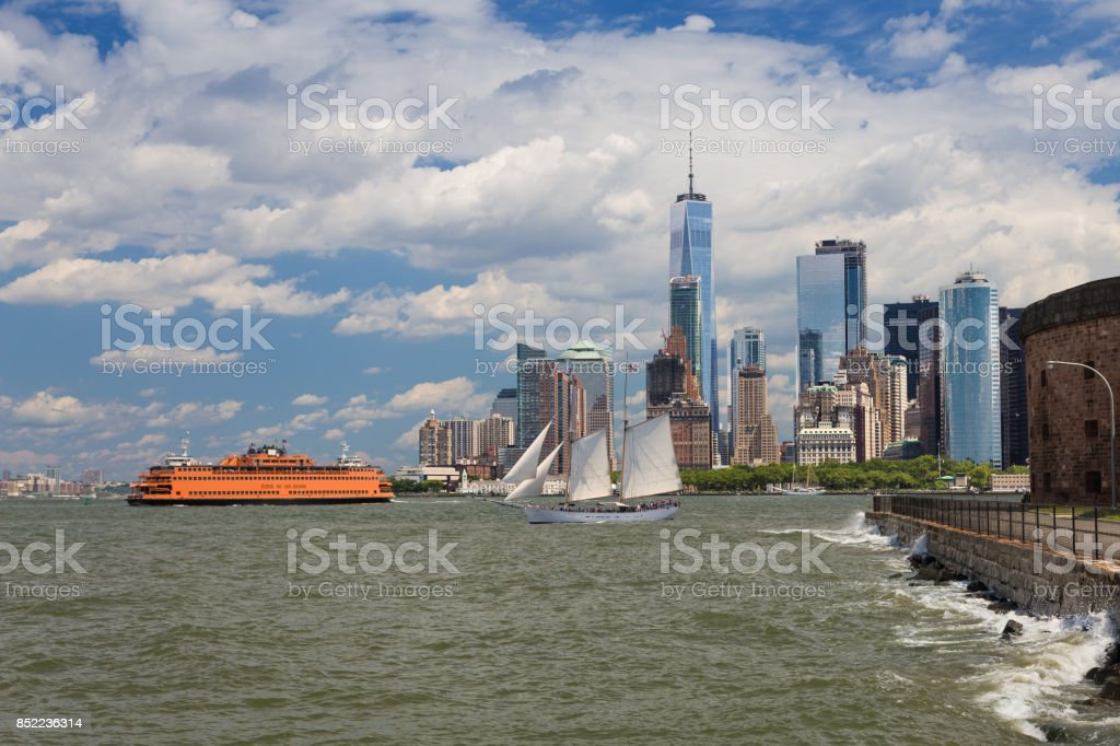 New York City Skyline with Manhattan Financial District, Governors Island, Sailboat (Tall Ship), Staten Island Ferry, Water of New York Harbor, World Trade Center and Blue Sky. stock photo