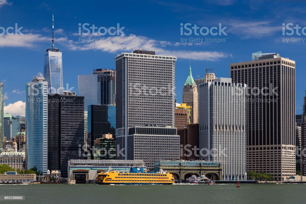 New York City Skyline with Manhattan Financial District, Water of New York Harbor, World Trade Center, Staten Island Ferry and Blue Sky. stock photo