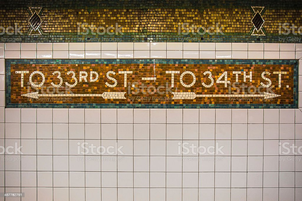 New York City subway sign showing street directions on tile stock photo