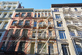New York houses facades with fire escape stairs, sunny day