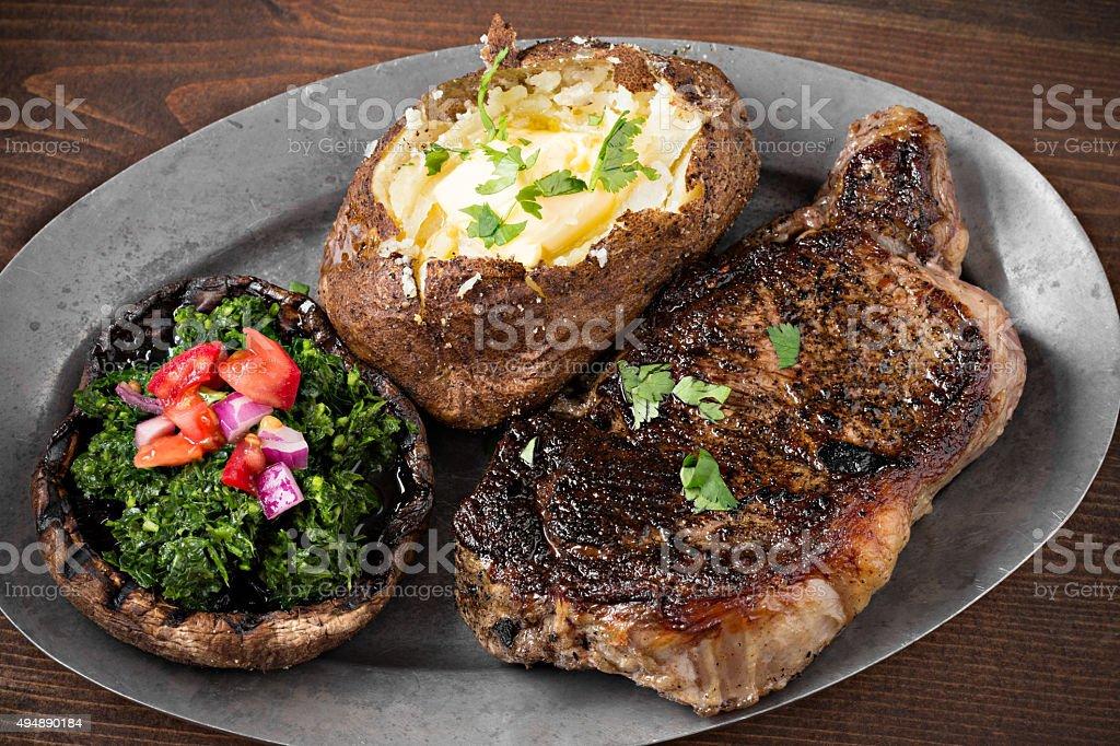 New York Steak, Baked Potato And Portobello Mushroom stock photo