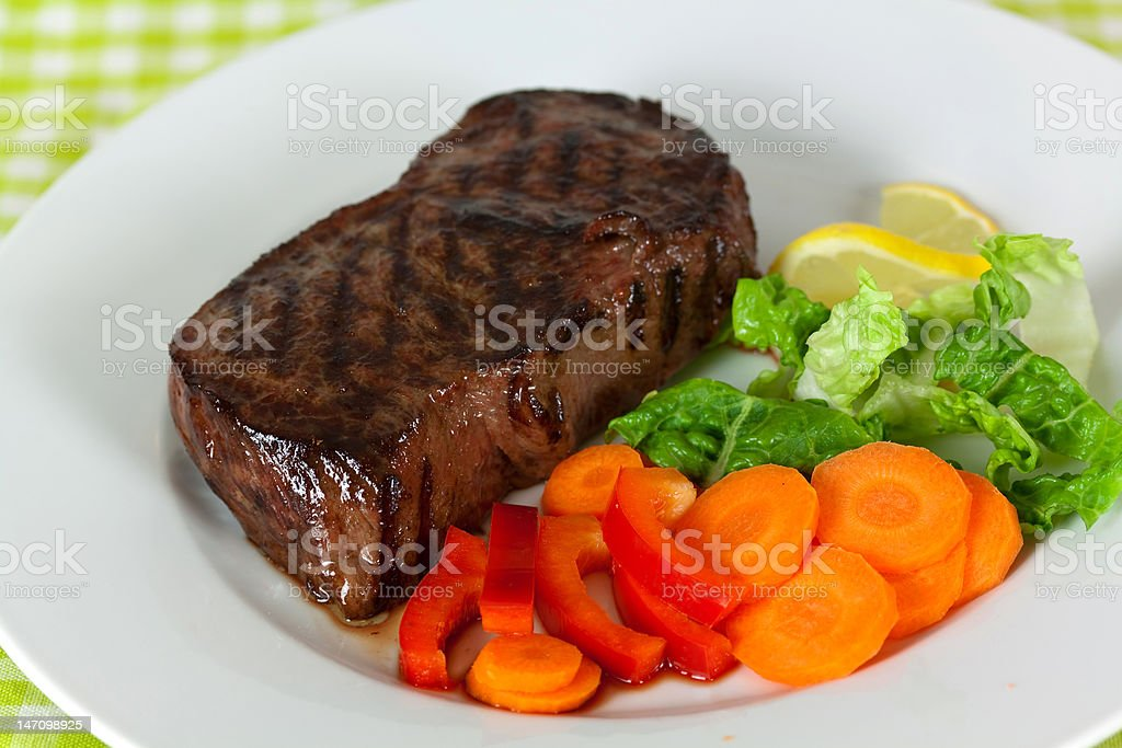 New York Steak- Carrot ,Pepper and green salad over plate royalty-free stock photo