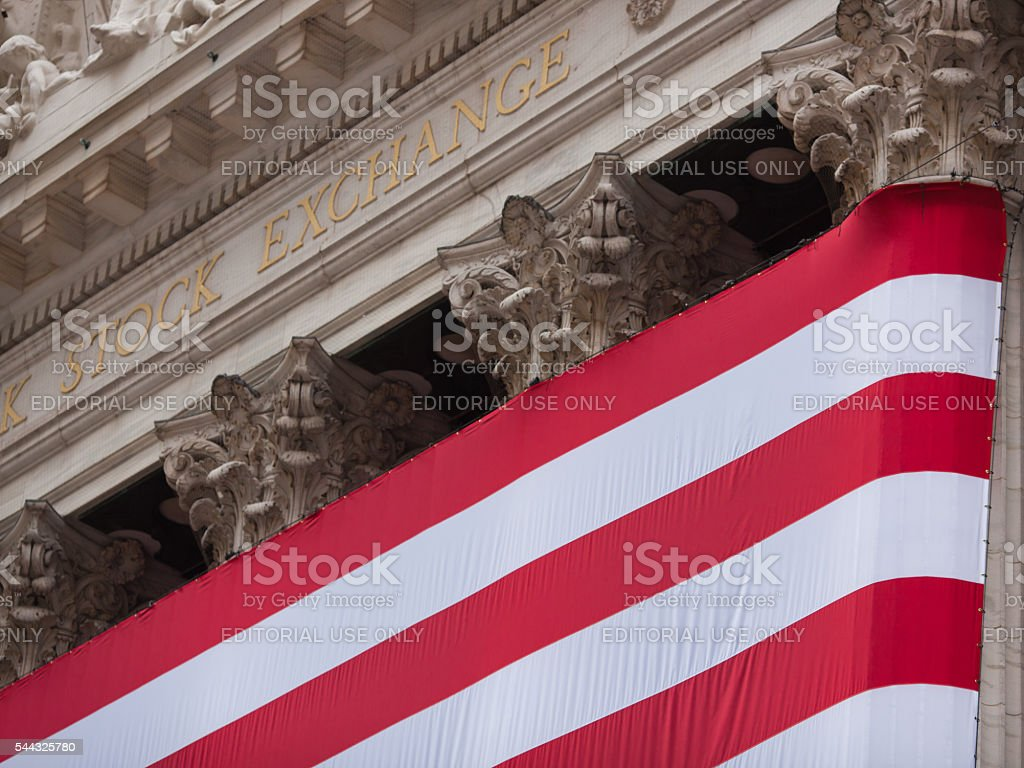 New York Stock Exchange building sign and large American flag stock photo
