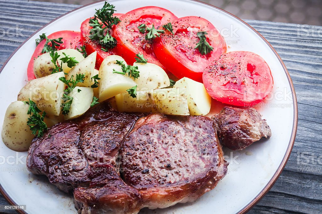 New York Strip Steak with boiled potatoes and fresh tomatoes stock photo