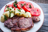 New York Strip Steak with boiled potatoes and fresh tomatoes