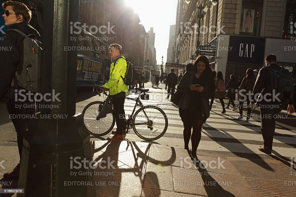 New Yorkers crossing 6th Avenue and 34th Street at sunrise stock photo