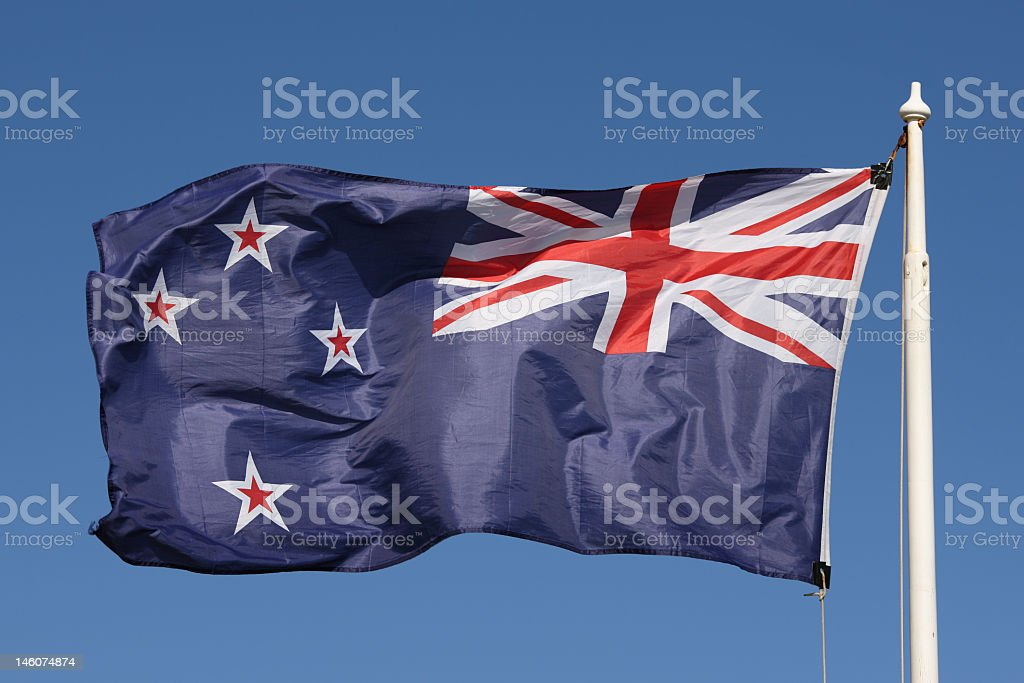 New Zealand flag in the air flying with clear blue sky stock photo