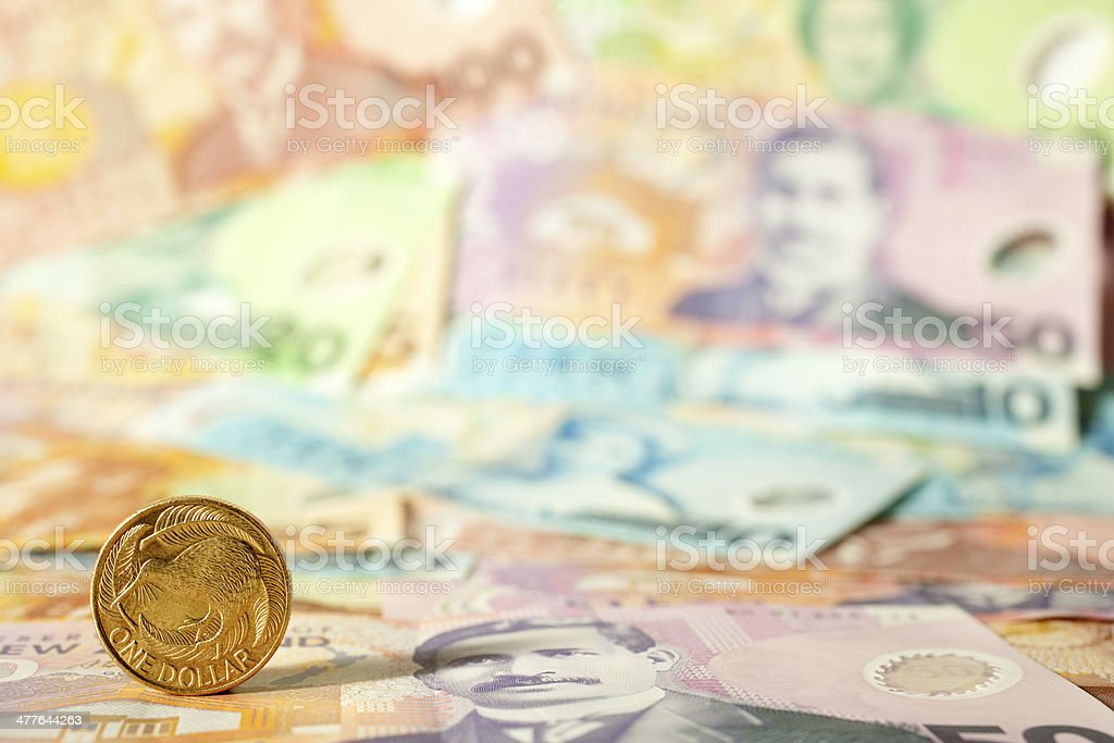 New Zealand One Dollar Coin on Banknote Background stock photo