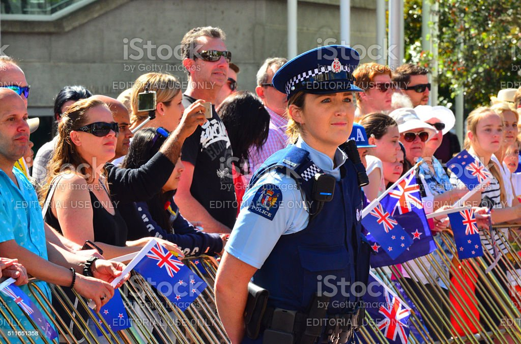 New Zealand police officer woman guarding crowd of people stock photo