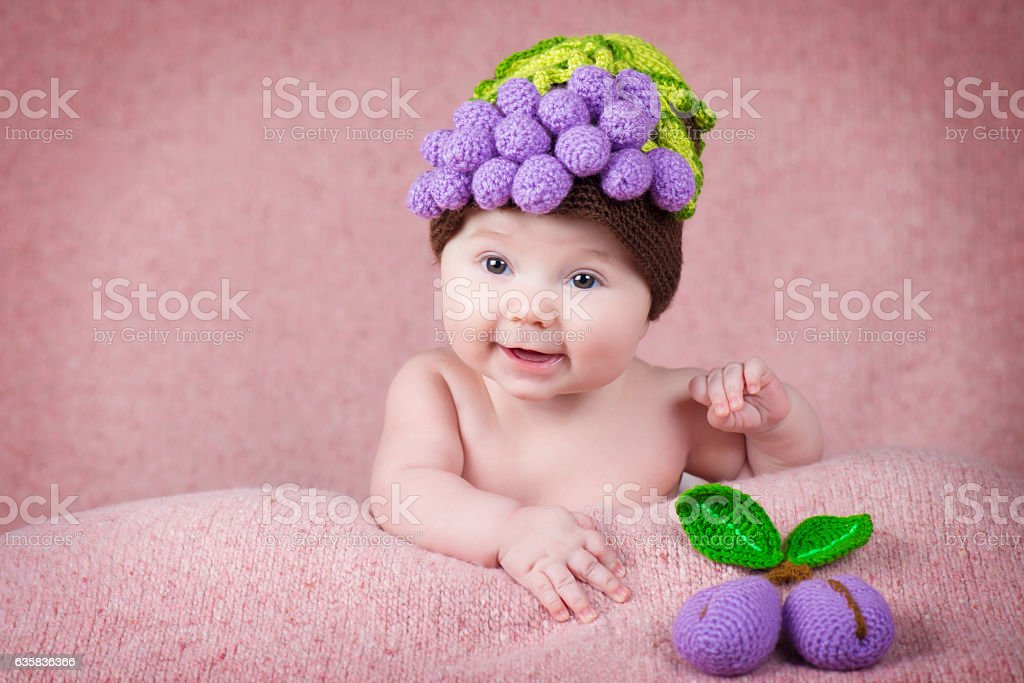 Newborn baby a knitted cap in the form of grapes. stock photo