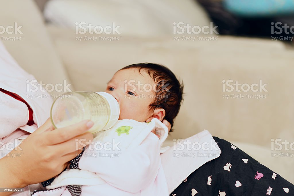 Newborn baby being held and fed from bottle. stock photo