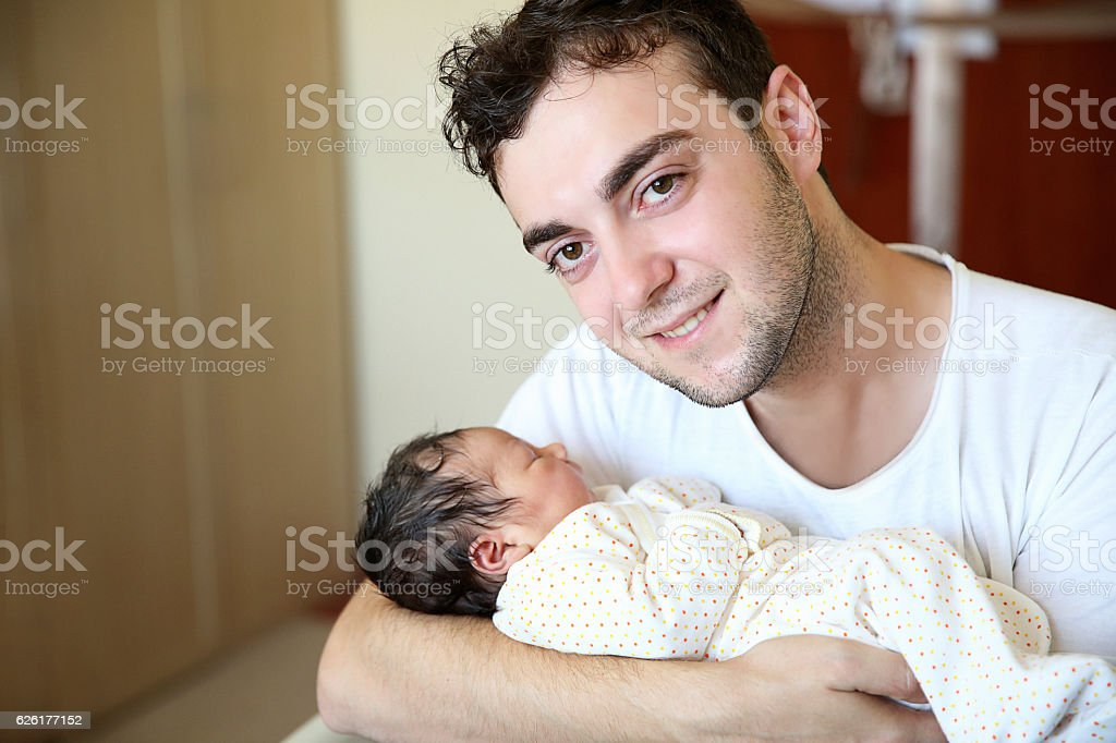 Newborn baby being held by their loving father stock photo