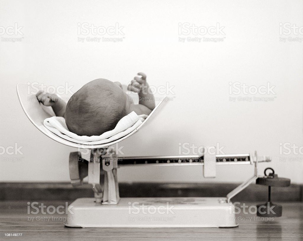 Newborn Baby Being Weighed on Vintage Scale, Black and White stock photo