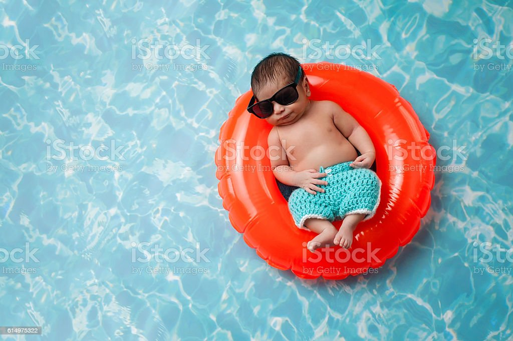 Newborn Baby Boy Floating on a Swim Ring stock photo
