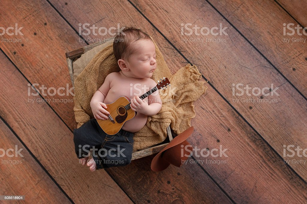 Newborn Baby Boy Playing a Tiny Guitar stock photo