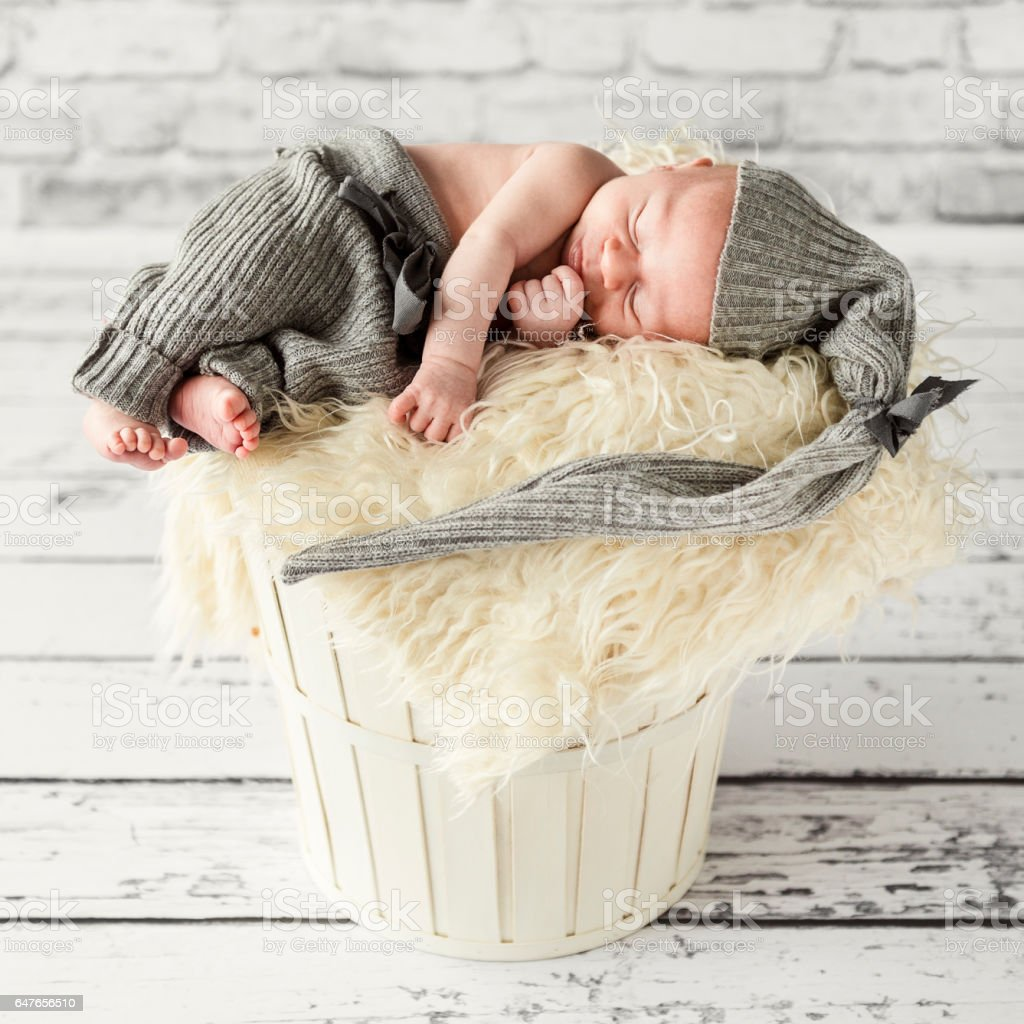 Newborn baby boy sleeping peacefully in wooden washtub, home interior stock photo