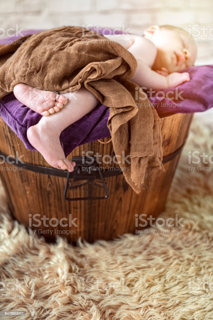 Newborn baby boy sleeping peacefully in wooden washtub, home interior stock photo